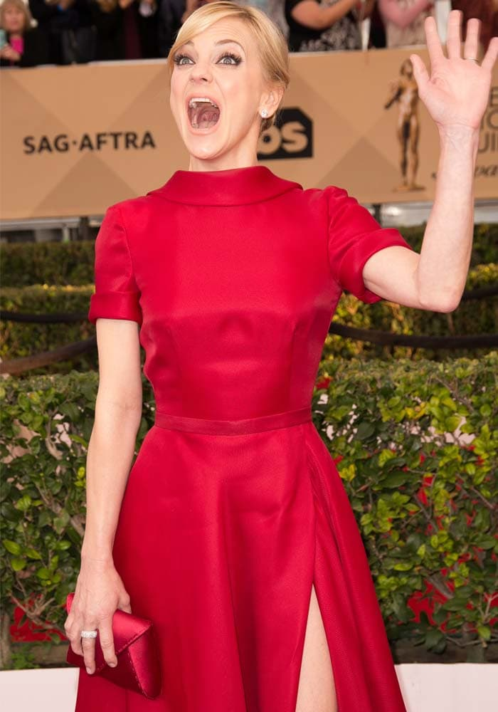 Anna Faris waves from the red carpet while wearing a sleeved gown from Naeem Khan