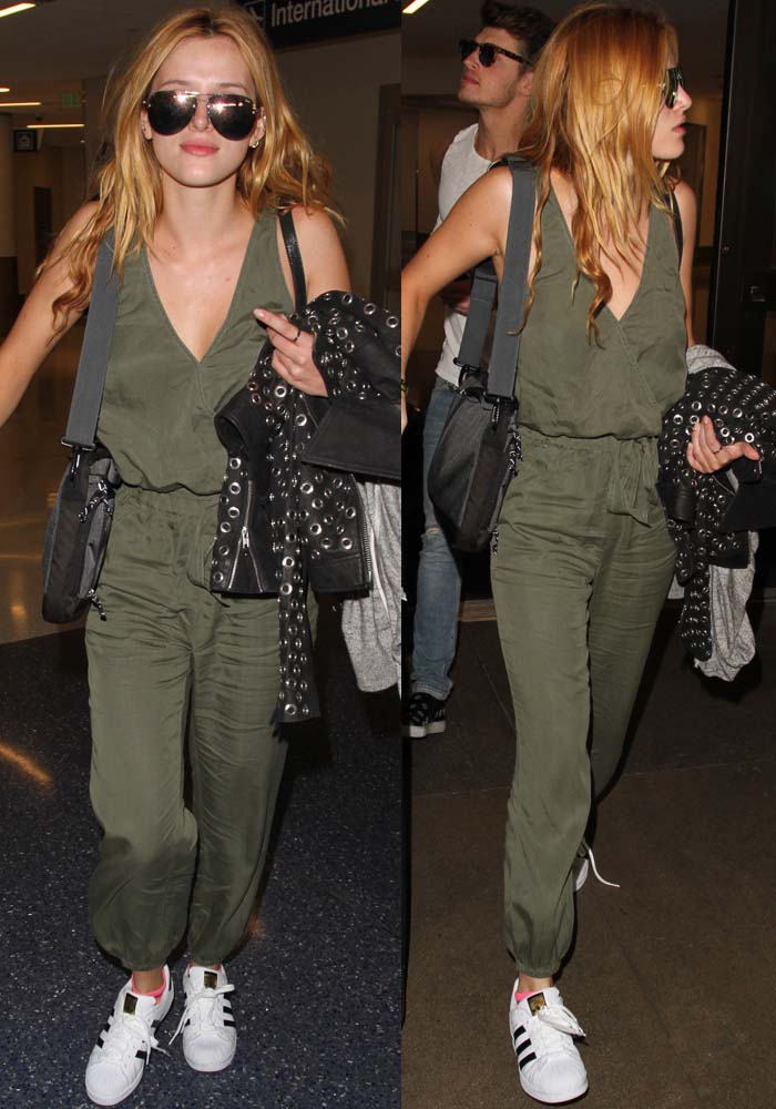 Bella Thorne wears an olive green jumpsuit and a pair of Adidas sneakers at LAX