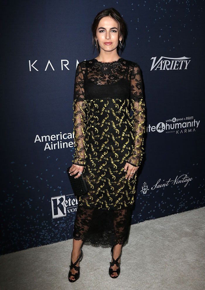 Camilla Belle wears a black-and-yellow Monique Lhuillier dress on the gray carpet
