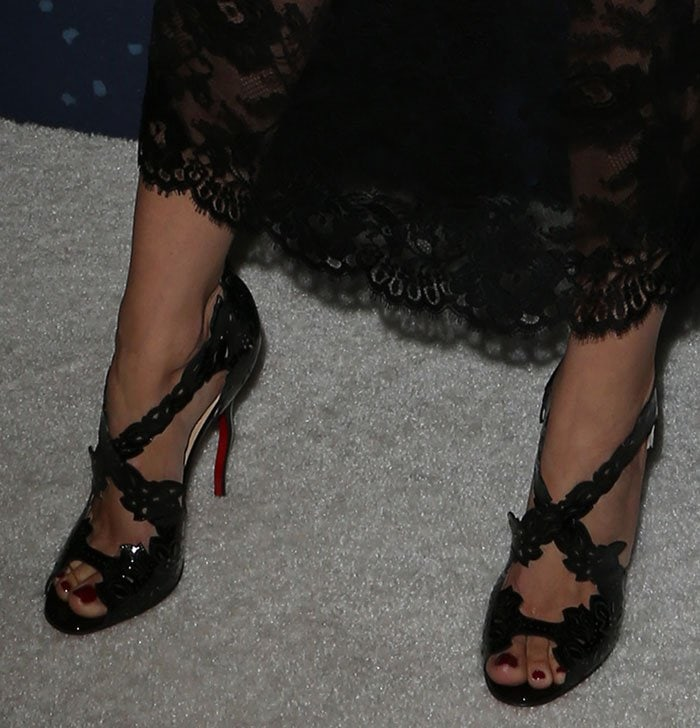 Camilla Belle's feet in black leather Christian Louboutin sandals