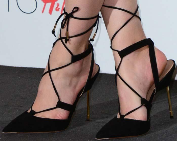 Charli XCX's feet in black lace-up Kurt Geiger pumps