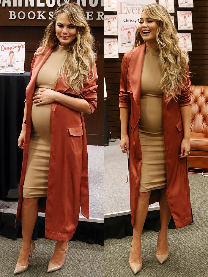 Chrissy Teigen poses with her growing baby bump in a Bossa dress