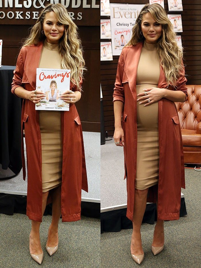 Chrissy Teigen holds a copy of her new cookbook and her growing baby bump