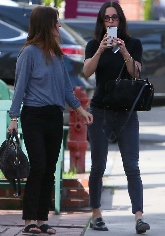 Courteney Cox photographs the paparazzi while leaving Le Pain Quotidien with a friend in Los Angeles