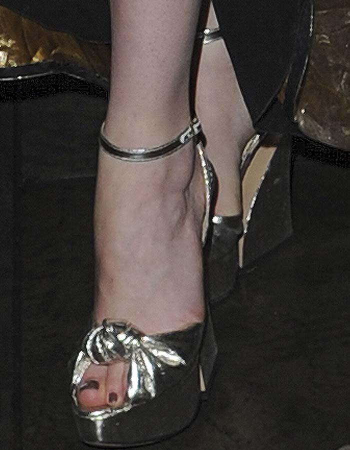 Dakota Johnson's feet in silver Charlotte Olympia platform sandals