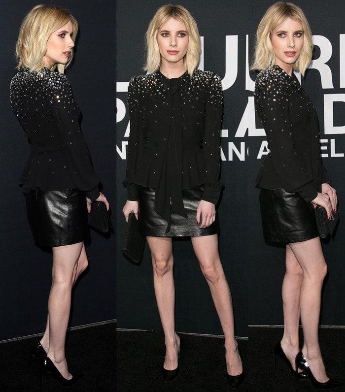 Emma Roberts wears a black Saint Laurent blouse with her black leather Saint Laurent mini skirt