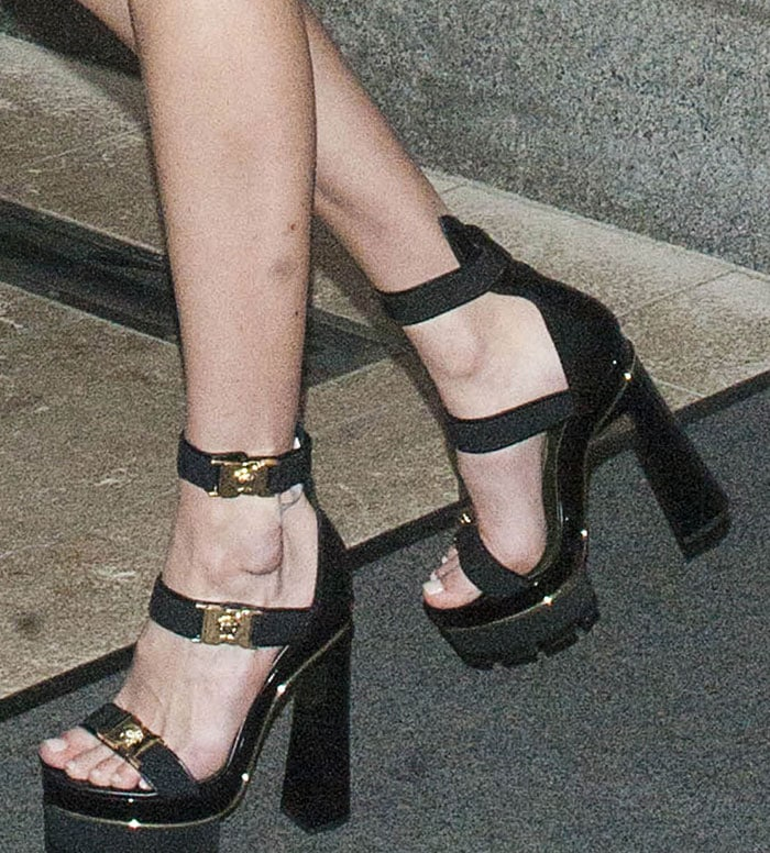 Gigi's sandals are also by Versace. They are made of leather and feature triple straps with logo-detailed buckle fastenings, gold-tone metal trims, 1.5-inch treaded rubber platforms and about 5.5-inch chunky heels.