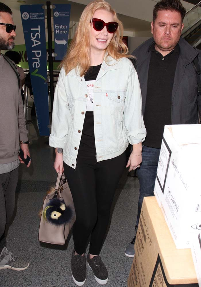 Iggy Azalea wears a Levi's jacket over a graphic t-shirt as she arrives at LAX