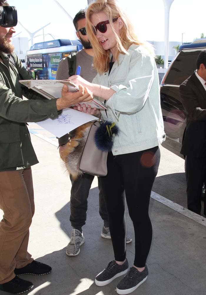 Iggy Azalea signs autographs for fans as she arrives at LAX