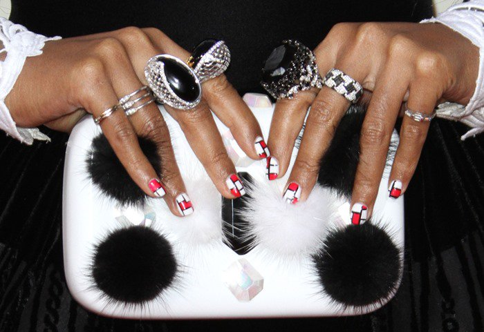 Janelle Monae shows off her Emm Kuo clutch and Carrera y Carrera and Levian rings at the Grammys