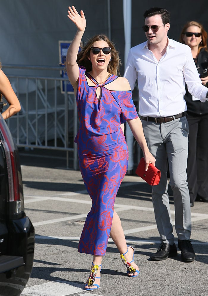 Jessica Biel waves while wearing a bright red-and-blue Roland Mouret dress