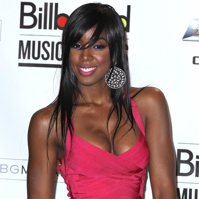 Kelly Rowland flashes her beautiful smile in a pink Herve Leger bandage dress