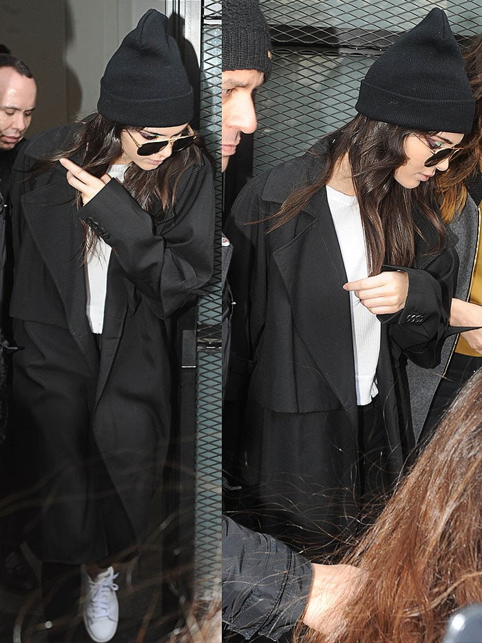Kendall Jenner wears a monochrome look including a beanie and aviators as she moves between Fendi and Versace fashion shows