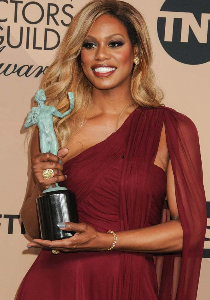 Laverne Cox shows off her Lorraine Schwartz jewelry as she poses with her award