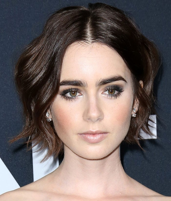 Lily Collins wore her brunette tresses in waves and sported smokey shadow and bold eyebrows