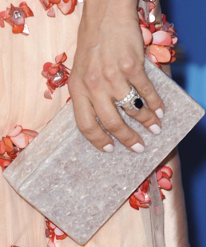 Mena Suvari holds a rectangular Edie Parker clutch