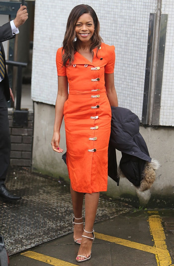 Naomie Harris carries a parka as she steps out in the cold, rainy London weather