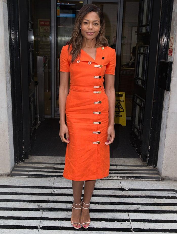 Naomie Harris shows how to wear a bright orange Altuzarra dress with nude heels in London
