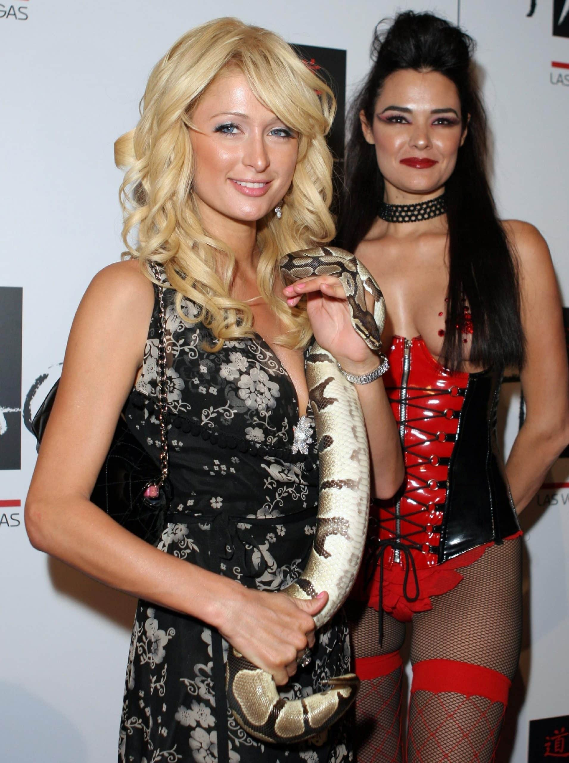 """Paris Hilton (L) holds a snake from Maria """"SnakeBabe"""" Gara at the Tao Las Vegas one-year anniversary celebration"""