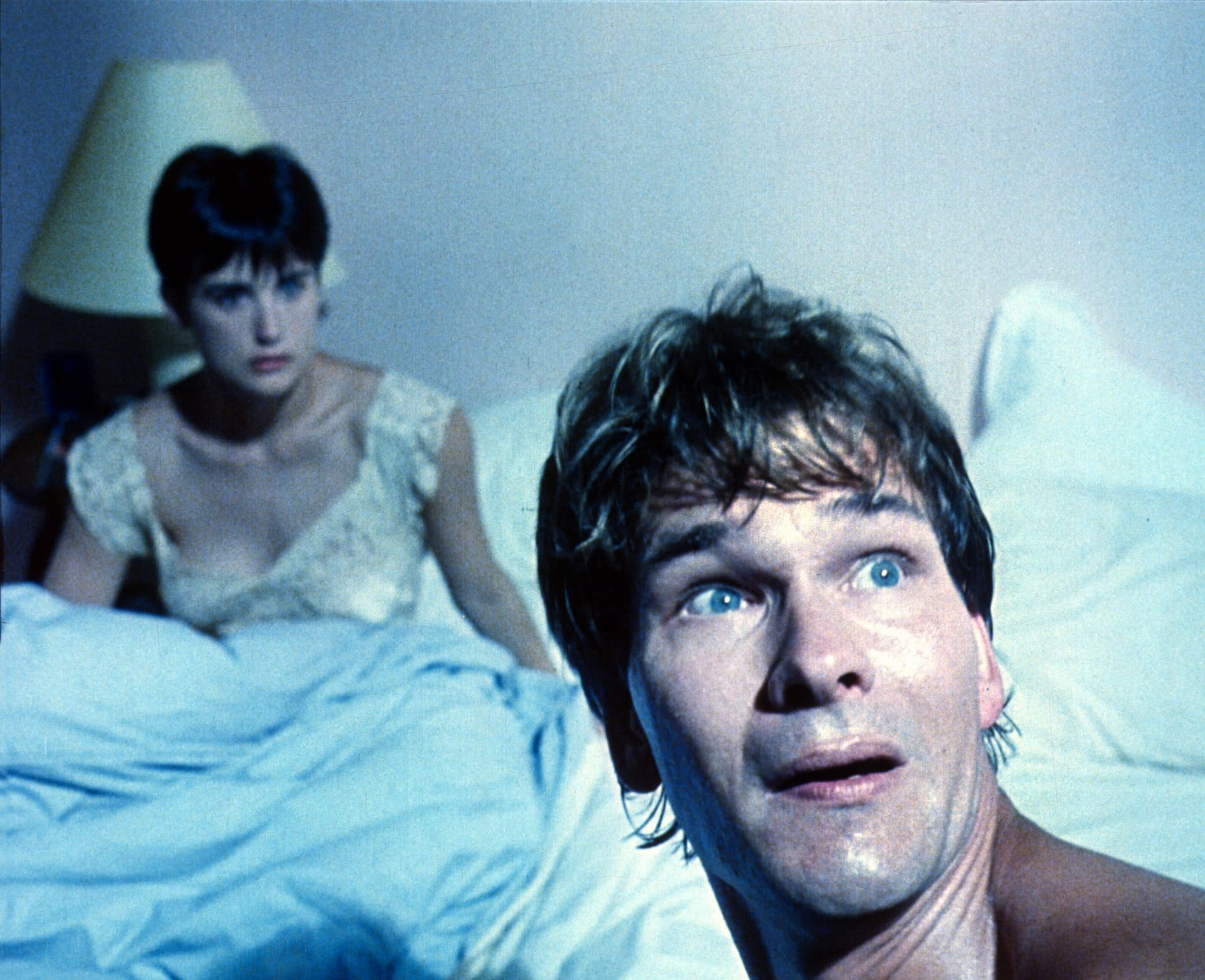 Patrick Swayze plays Sam Wheat, a murdered banker whose ghost sets out to save his girlfriend (Demi Moore as Molly Jensen) from the person who killed him, in Ghost