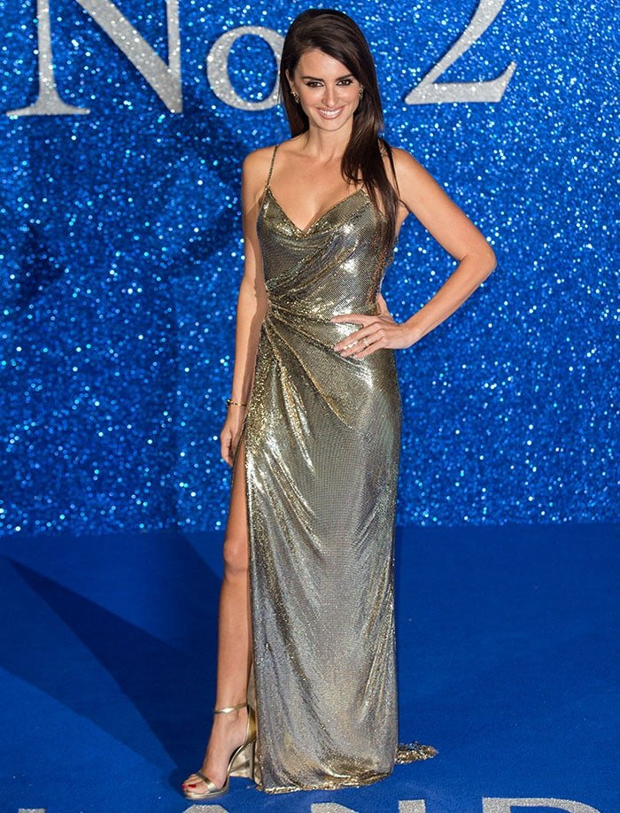 Penelope Cruz pairs her gold Atelier Versace dress with a pair of gold sandals