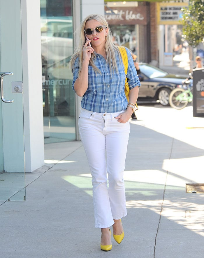 Reese Witherspoon wears a blue shirt and white jeans from her own clothing line, Draper James