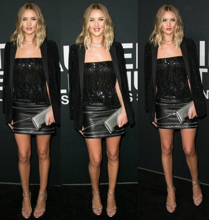 Rosie Huntington-Whiteley wears a sequined top and a sparkling suit jacket with a leather Saint Laurent mini skirt
