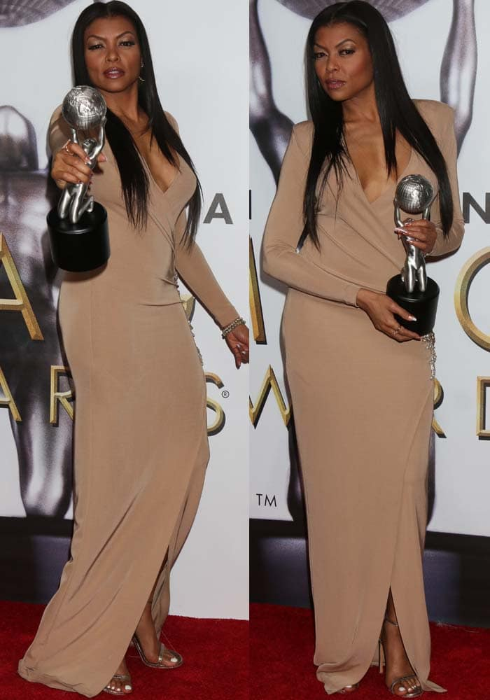 Taraji P. Henson holds her award while wearing a neutral-colored dress by Balmain