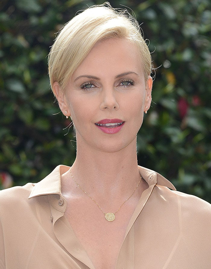 Charlize Theron's side-swept hair and dark pink lipstick