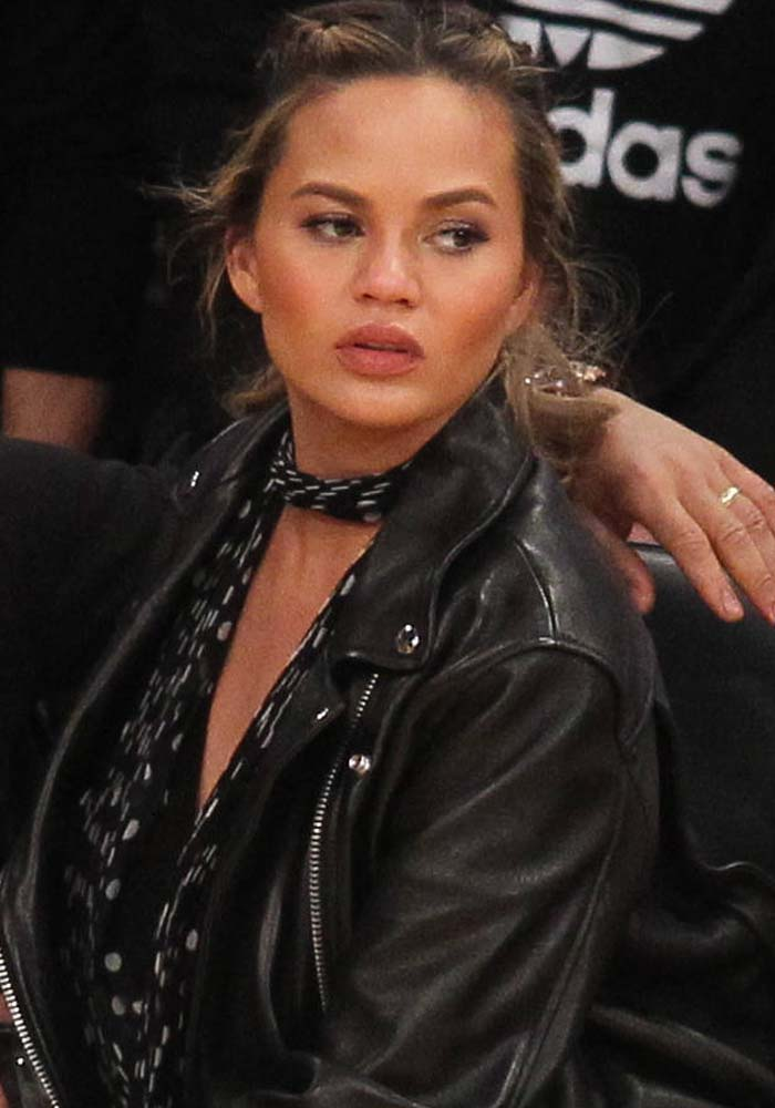 Chrissy Teigen braids her hair for the Los Angeles Lakers game against the Cleveland Cavaliers