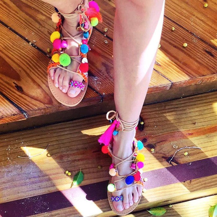 Semi-precious stones, pom-poms, and colorful embroidery accent the straps of these flat Elina Linardaki sandals.