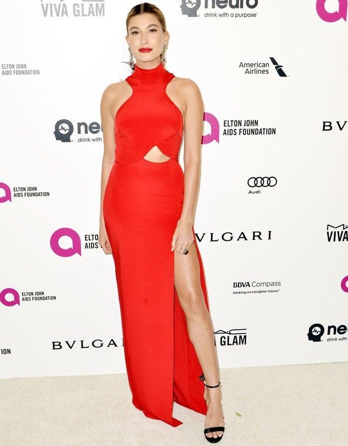 Hailey Baldwin wears a show-stopping red Gabriela Cadena dress with matching lipstick