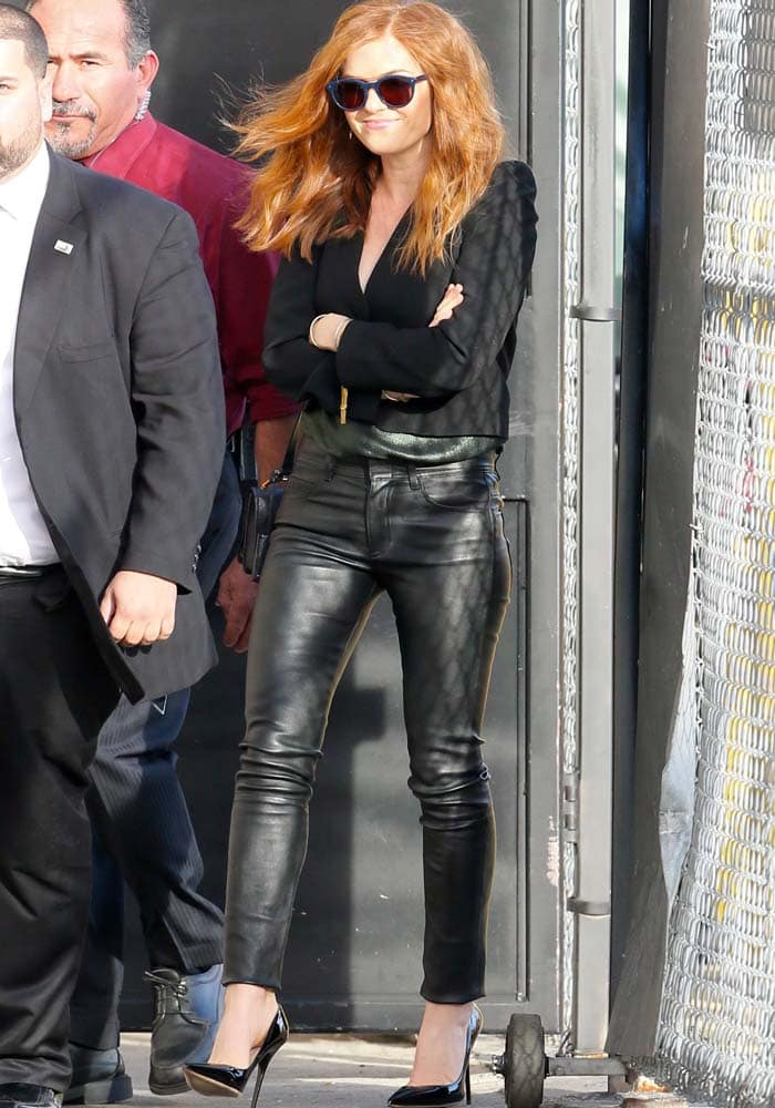 Isla Fisher wears black leather pants with a plunging metallic green top and puffed-sleeve blazer