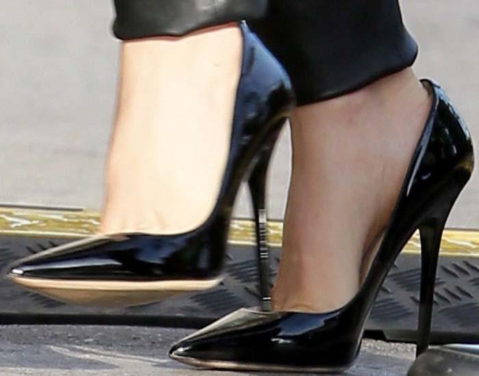 Isla Fisher's feet in black patent Jimmy Choo pumps