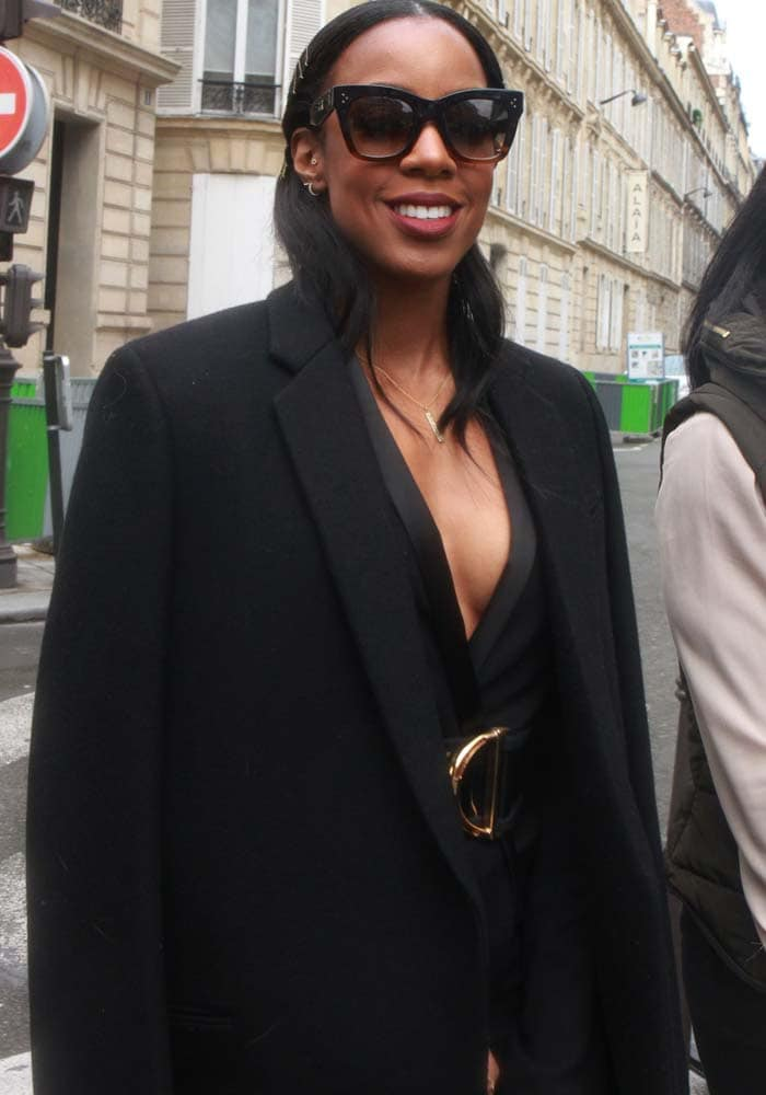 Kelly Rowland clips her hair back as she leaves a Paris restaurant
