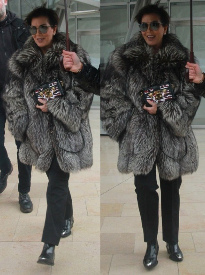 Kris Jenner hides from the Paris weather on her way to the Luis Vuitton show during Paris Fashion Week on March 9, 2016