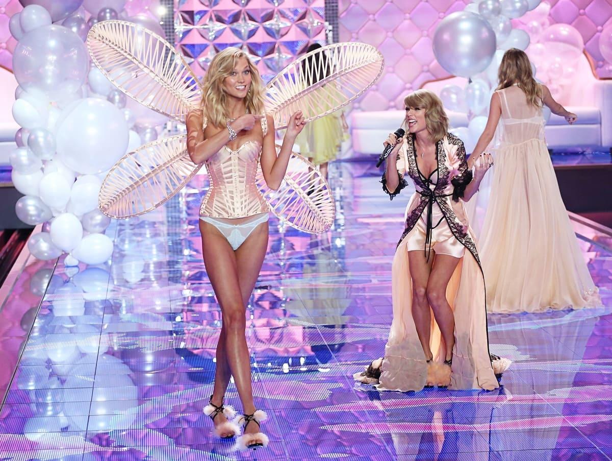 Model Karlie Kloss (L) walks the runway as singer Taylor Swift performs