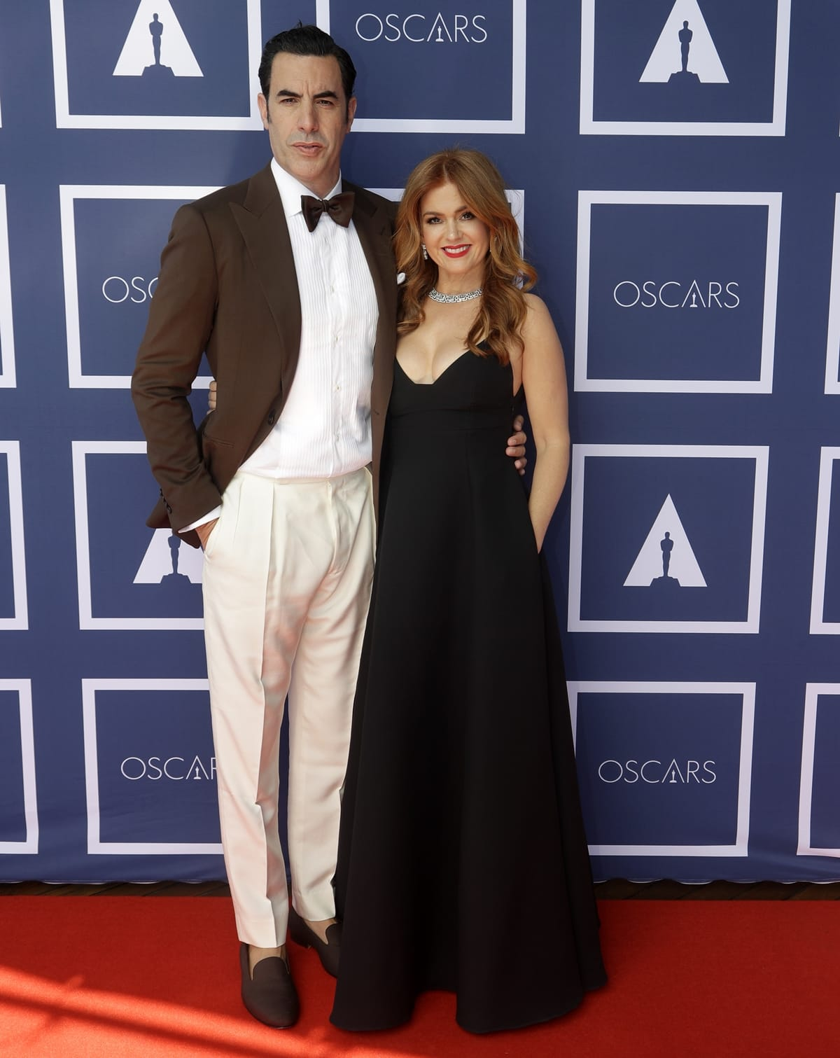 Isla Fisher in a black low-cut black Dior gown and her husband Sacha Baron Cohen