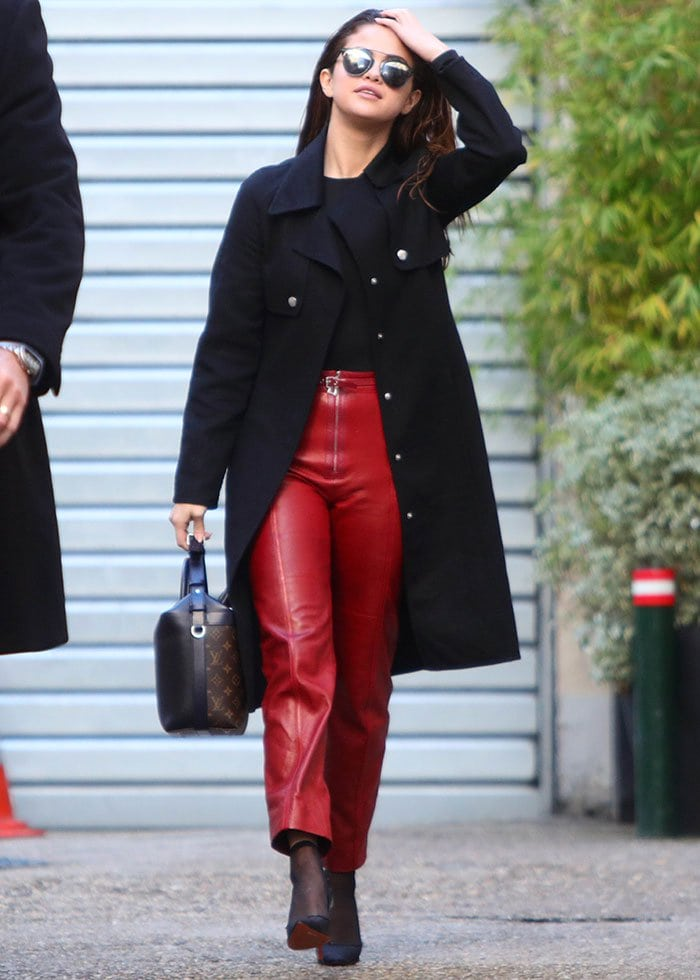 Selena Gomez brushes her hair back as she leaves a photo studio in Paris