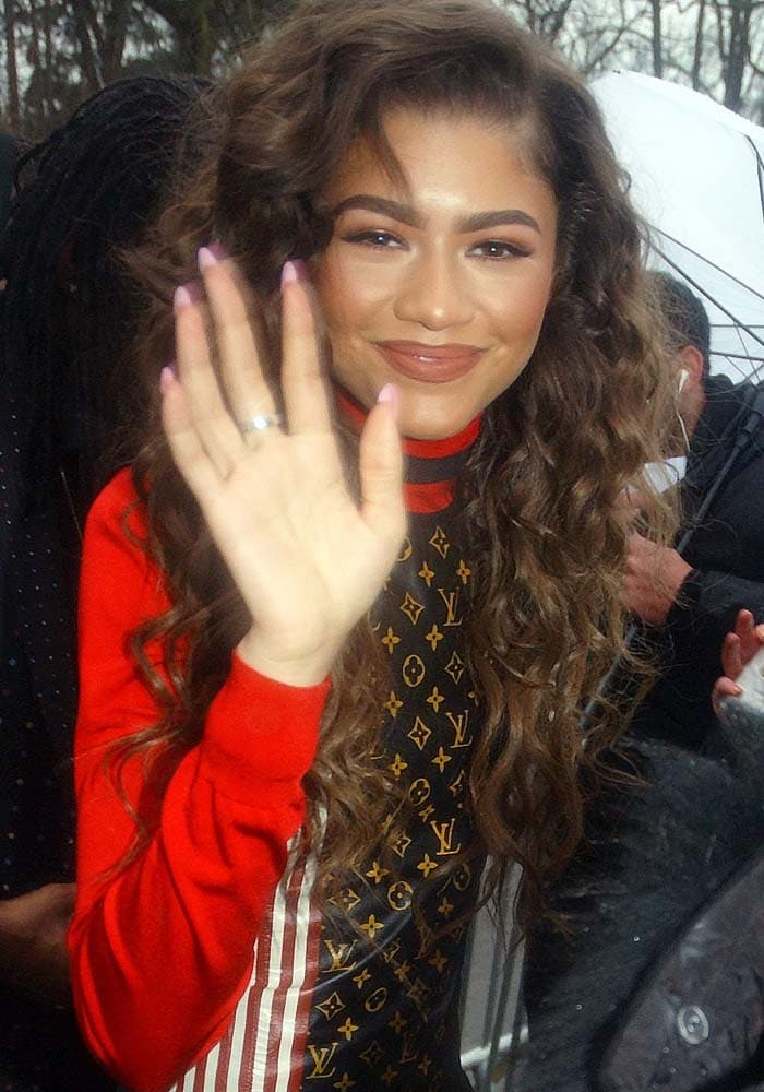 Zendaya smiles and waves after being accidentally hit with an umbrella