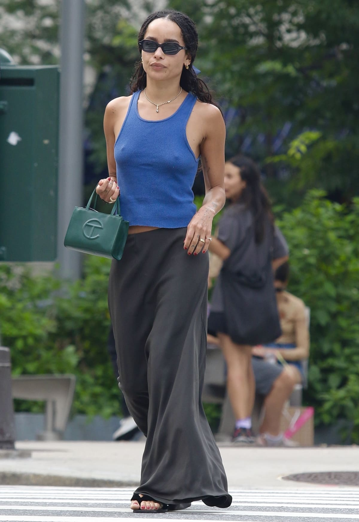 Zoe Kravitz shows how to wear a maxi skirt with a blue tank top, square toe sandals, and a green Telfar bag