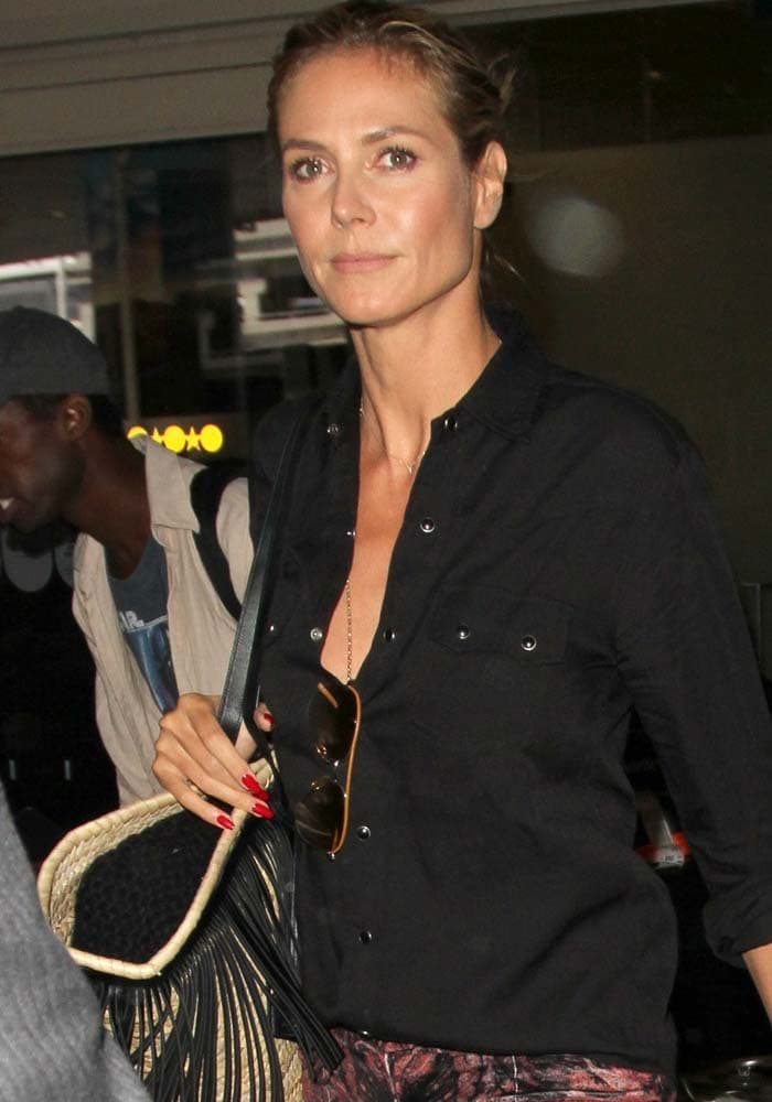 Heidi Klum wearing a chic unbuttoned black blouse while arriving at Los Angeles International Airport