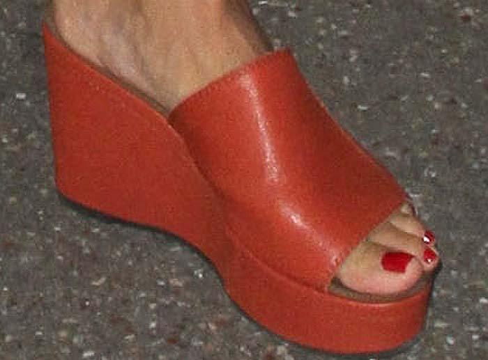 Heidi Klum slips into a pair of orange flatforms