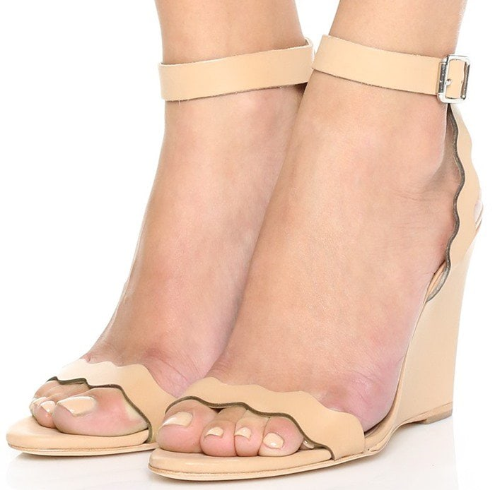 Scalloped curves lend a touch of feminine whimsy to a minimalist wedge sandal secured with a sleek, buckled ankle strap
