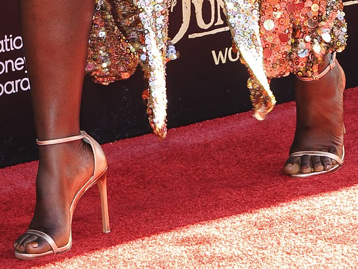Gold Stuart Weitzman 'Nudist' sandals on Lupita Nyong'o's feet