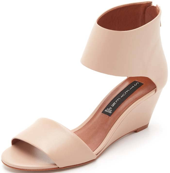 A bold ankle cuff and wrapped wedge heel amplify the contemporary sophistication of a clean, minimalist sandal in smooth leather.