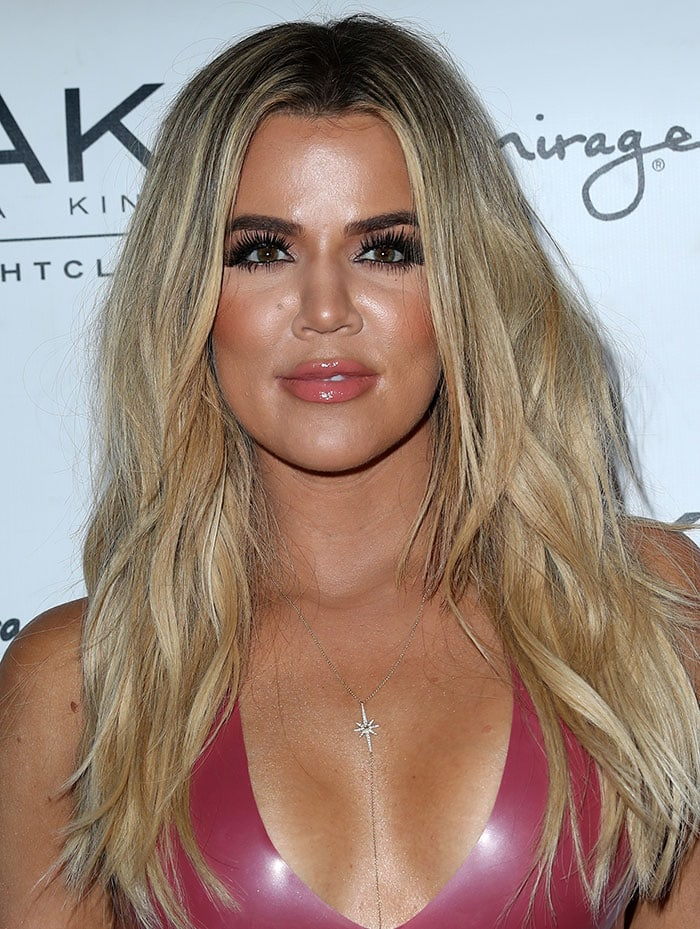 Khloe Kardashian wore her signature blonde tresses down in simple, tousled waves with a center part, and sported nude lipstick and long, dark lashes