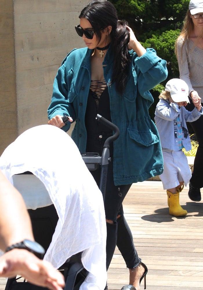 Kim Kardashian wearing an oversized aqua-colored denim jacket over a black lace-up top