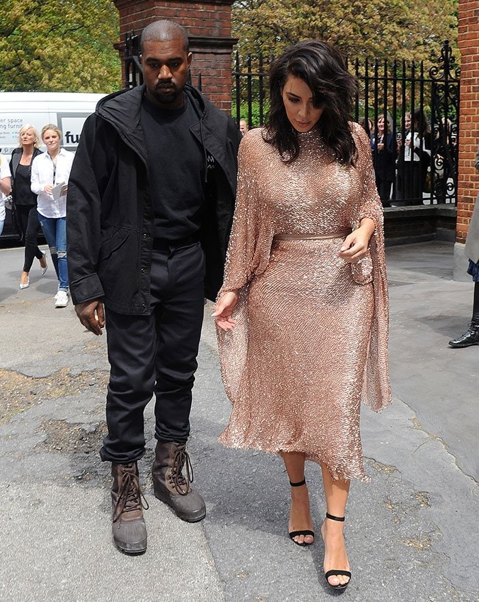 Kanye Westdressed down in a black parka jacket, a black tee, pants and lace-up boots
