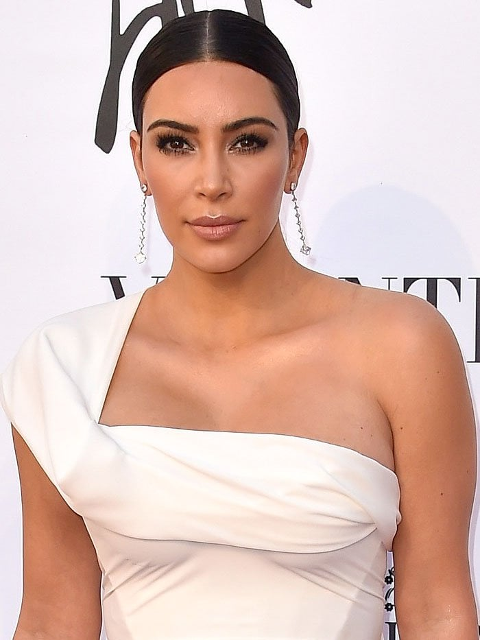 Kim Kardashian sporting a slicked-down center-parted hairdo, heavy lashes, and dangling diamond earrings